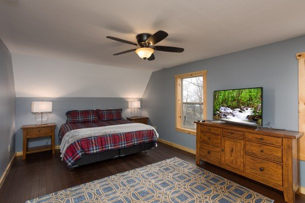 King bed, dresser, and TV in the main floor bedroom at Pigeon Forge Panorama, a 2 bedroom cabin rental located in Pigeon Forge
