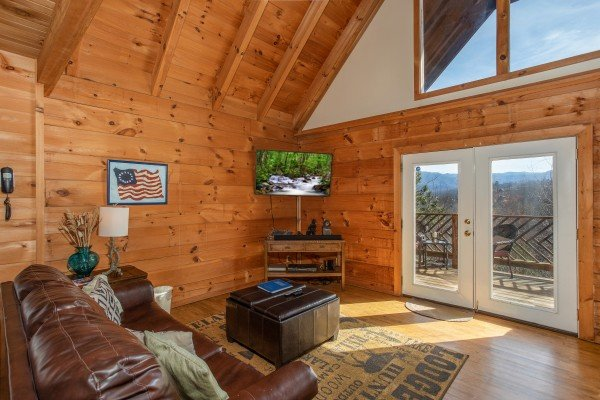 Living room with TV and deck access at Brink of Heaven, a 2-bedroom cabin rental located in Gatlinburg