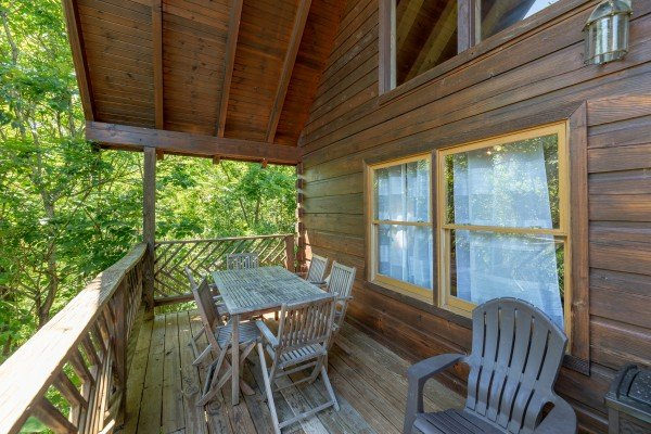 Dining set for six on the covered deck at Brink of Heaven, a 2 bedroom cabin rental located in Gatlinburg