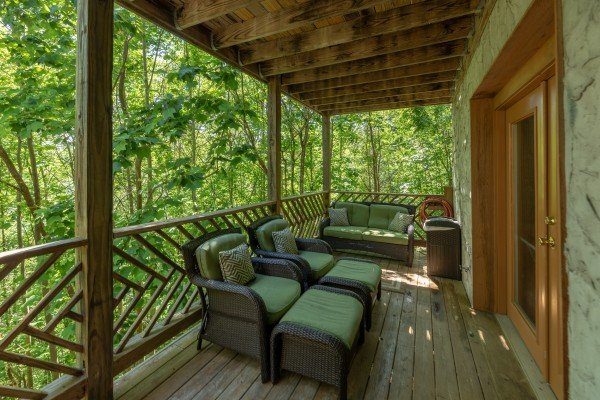 Comfy seating on the covered deck at Brink of Heaven, a 2 bedroom cabin rental located in Gatlinburg