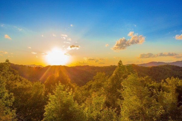 Bright sunshine over a mountain range at Sweet Serenity, a 2 bedroom cabin rental located in Gatlinburg