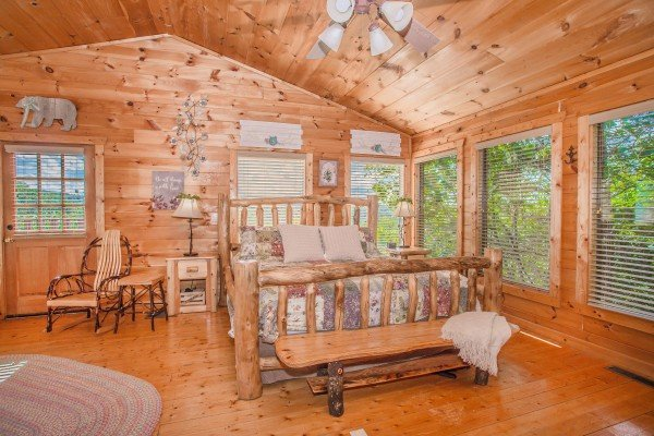Bedroom with a log bed, bench, and rocking chair at Sweet Serenity, a 2 bedroom cabin rental located in Gatlinburg