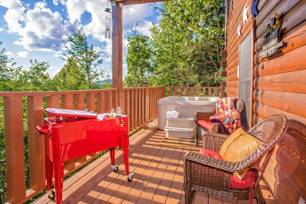 Covered porch with drink cooler, hot tub, and chairs at Sweet Serenity, a 2 bedroom cabin rental located in Gatlinburg