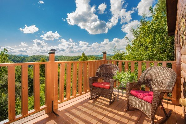Wicker rocking chairs on a deck at Sweet Serenity, a 2 bedroom cabin rental located in Gatlinburg