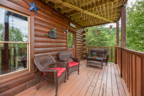 Wicker deck seating on a covered deck at Sweet Serenity, a 2 bedroom cabin rental located in Gatlinburg