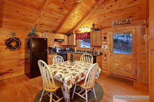 kitchen and dining area at scenic mountain view a 1 bedroom cabin rental located in pigeon forge
