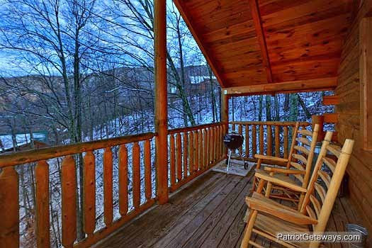 main level deck with rockers and grill at scenic mountain view a 1 bedroom cabin rental located in pigeon forge