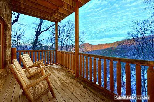 rear deck with chairs at scenic mountain view a 1 bedroom cabin rental located in pigeon forge