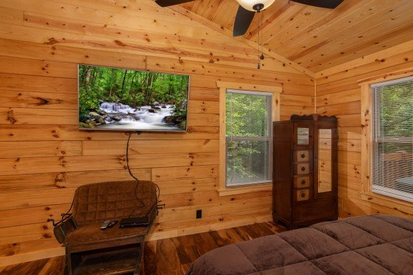 TV, chair, and armoire in the bedroom at Paws on the Porch, a 2 bedroom cabin rental located in Gatlinburg