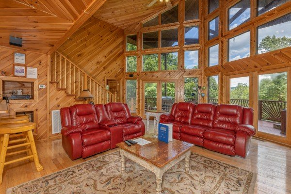 Living room with sofa, loveseat, and high windows at Kaleidoscope, a 2 bedroom cabin rental located in Pigeon Forge