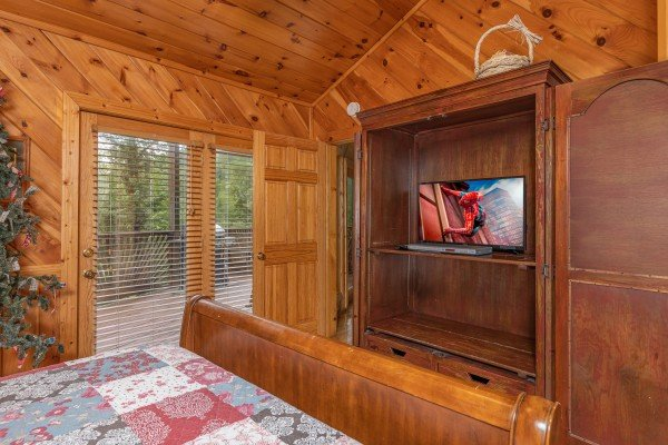 Armoire, TV, and deck access in a bedroom at Kaleidoscope, a 2 bedroom cabin rental located in Pigeon Forge