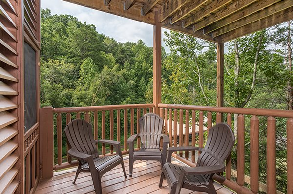 Adirondack chairs on a covered porch at At Home in the Woods, a 3-bedroom cabin rental located in Pigeon Forge