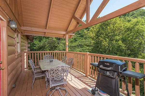 Dining table on a covered deck with a propane grill at At Home in the Woods, a 3-bedroom cabin rental located in Pigeon Forge