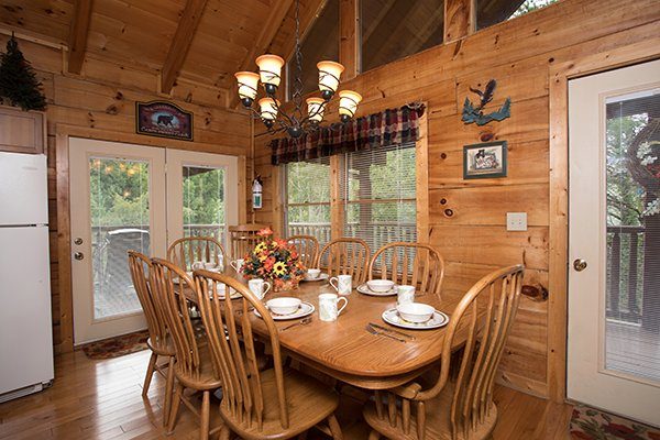 Dining table with seating for eight at At Home in the Woods, a 3-bedroom cabin rental located in Pigeon Forge