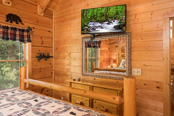 Wall-mounted television above a mirror at At Home in the Woods, a 3-bedroom cabin rental located in Pigeon Forge