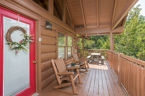 Front porch with wooden rockers at At Home in the Woods, a 3-bedroom cabin rental located in Pigeon Forge