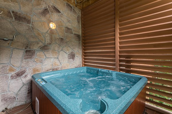 Hot tub with privacy fence at At Home in the Woods, a 3-bedroom cabin rental located in Pigeon Forge