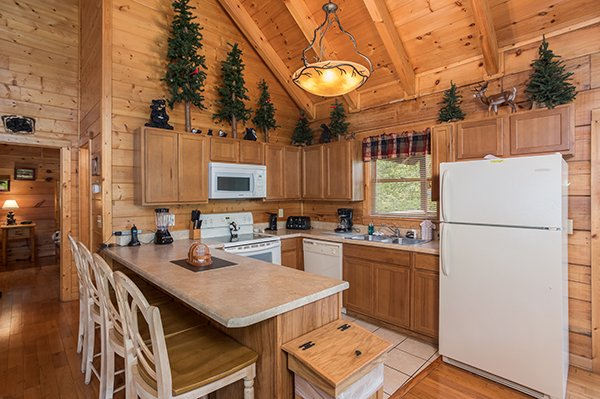 Kitchen with white appliances and counter seating for three at At Home in the Woods, a 3-bedroom cabin rental located in Pigeon Forge