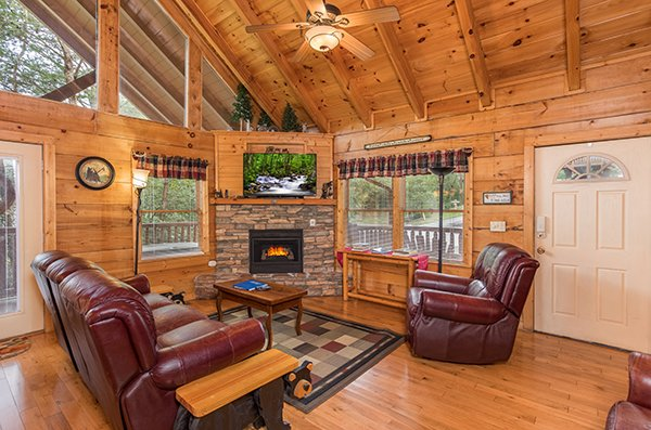 Living room with leather couch and recliner, stone fireplace and wall-mounted television at At Home in the Woods, a 3-bedroom cabin rental located in Pigeon Forge