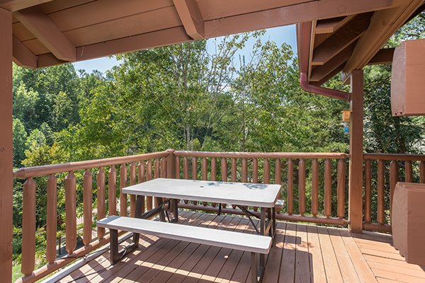 Picnic table on a deck at At Home in the Woods, a 3-bedroom cabin rental located in Pigeon Forge