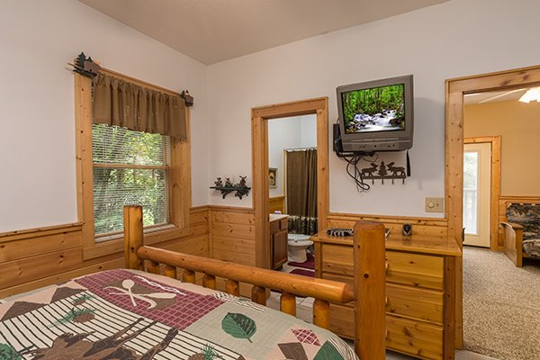 Bedroom with wall-mounted television and attached bath at At Home in the Woods, a 3-bedroom cabin rental located in Pigeon Forge