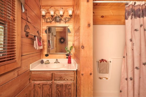 Bathroom with vanity and a tub and shower at Hidden Hideaway, a 3-bedroom cabin rental located in Pigeon Forge