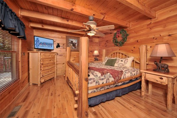 Bedroom with a four post bed, dresser, and TV at Hidden Hideaway, a 3-bedroom cabin rental located in Pigeon Forge
