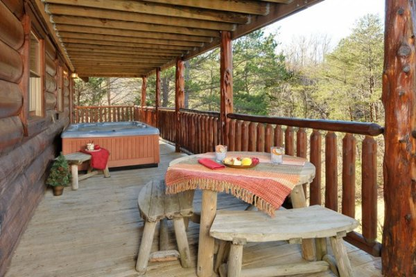 Covered deck with a dining table and a hot tub at Hidden Hideaway, a 3-bedroom cabin rental located in Pigeon Forge
