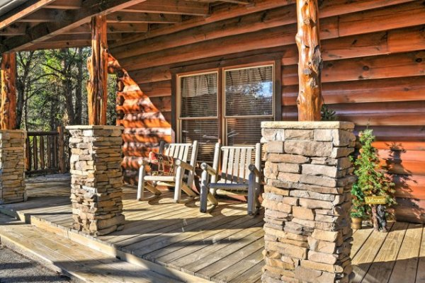 Covered front porch with rocking chairs at Hidden Hideaway, a 3-bedroom cabin rental located in Pigeon Forge
