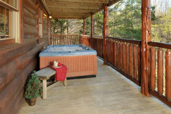 Hot tub on a covered deck at Hidden Hideaway, a 3-bedroom cabin rental located in Pigeon Forge