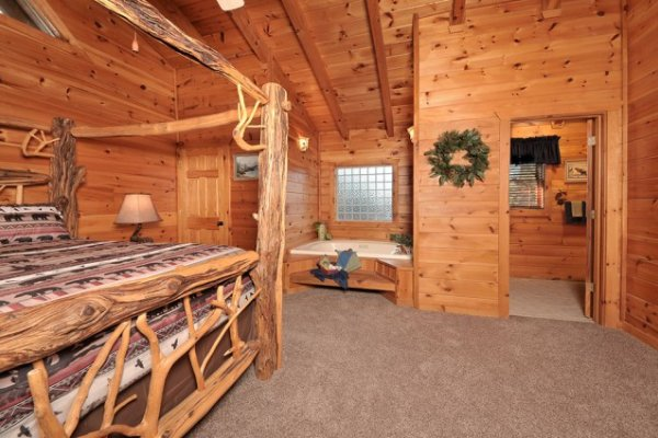 Bedroom with a king canopy bed, in room jacuzzi, and en suite bath at Hidden Hideaway, a 3-bedroom cabin rental located in Pigeon Forge