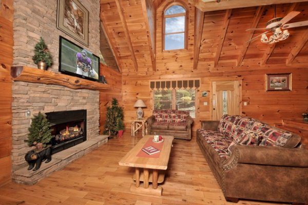 Living room with stone fireplace, TV, and large window at Hidden Hideaway, a 3-bedroom cabin rental located in Pigeon Forge