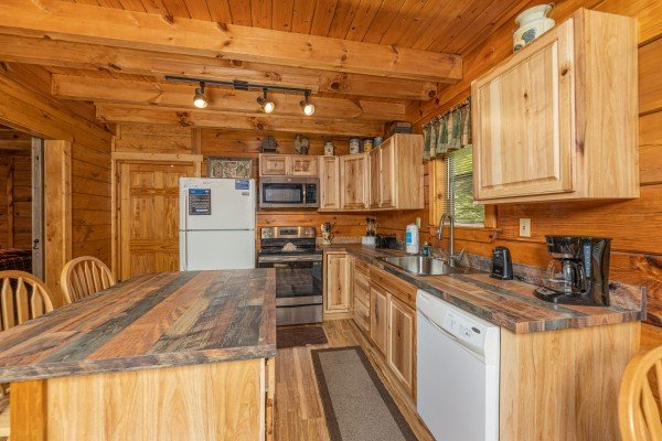 Kitchen with white and stainless appliances at Honeymoon in Gatlinburg, a 1 bedroom cabin rental located in Gatlinburg