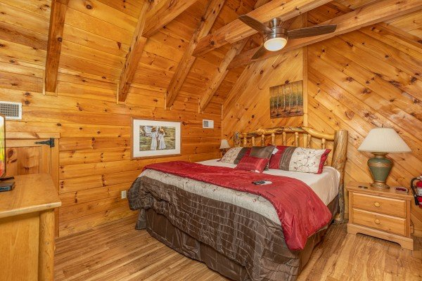 Loft bedroom with a night stand and lamp at Honeymoon in Gatlinburg, a 1 bedroom cabin rental located in Gatlinburg