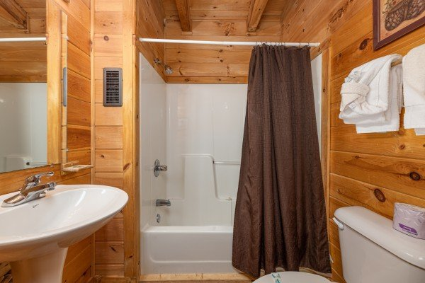 Bathroom with a tub and shower at Honeymoon in Gatlinburg, a 1 bedroom cabin rental located in Gatlinburg