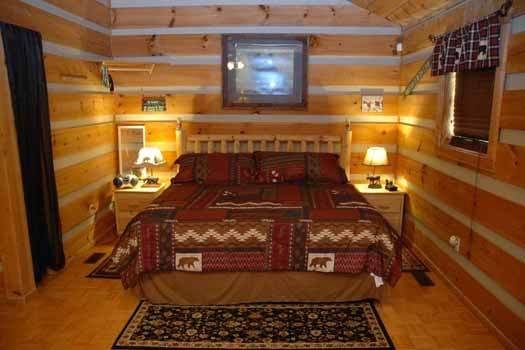 bedroom of studio layout with king sized bed at a point of view a 1 bedroom cabin rental located in pigeon forge