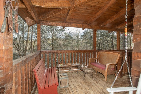 Benches on the covered deck at Sassafras Lodge, a 3 bedroom cabin rental located in Gatlinburg
