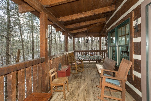 Benches and rocking chairs on the covered deck at Sassafras Lodge, a 3 bedroom cabin rental located in Gatlinburg