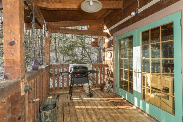 Grill on a covered deck at Sassafras Lodge, a 3 bedroom cabin rental located in Gatlinburg