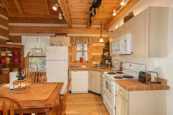 Kitchen with white appliances at Sassafras Lodge, a 3 bedroom cabin rental located in Gatlinburg