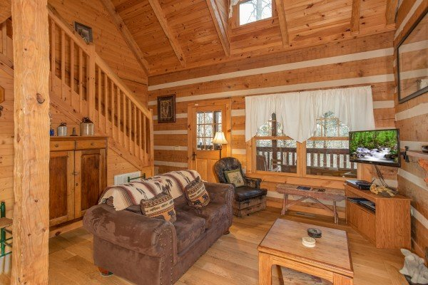 Sofa, glider, and TV in a living room at Sassafras Lodge, a 3 bedroom cabin rental located in Gatlinburg
