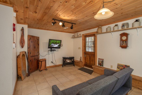 TV and electric fireplace in a lower level living room at Sassafras Lodge, a 3 bedroom cabin rental located in Gatlinburg