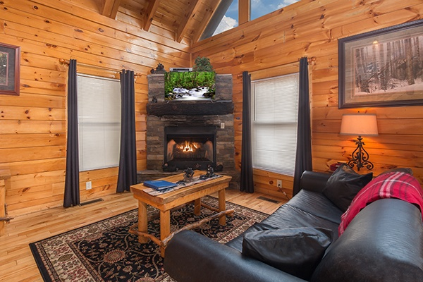 Living room with a fireplace, television, and leather sofa at Country Bear's Getaway, a 3-bedroom cabin rental located in Gatlinburg