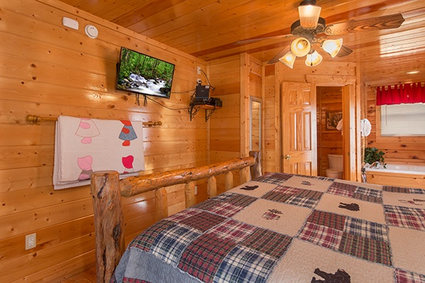 King-sized bedroom with a television, in room jacuzzi, and en suite bath at Country Bear's Getaway, a 3-bedroom cabin rental located in Gatlinburg