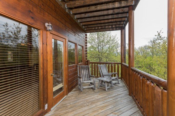 Two log rocking chairs on a covered deck at Howlin' in the Smokies, a 2 bedroom cabin rental located in Pigeon Forge