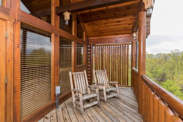 Covered deck with privacy fence and two rocking chairs at Howlin' in the Smokies, a 2 bedroom cabin rental located in Pigeon Forge