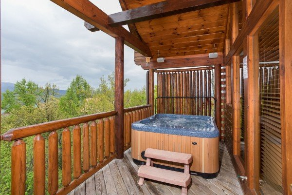 Hot tub on a covered deck at Howlin' in the Smokies, a 2 bedroom cabin rental located in Pigeon Forge