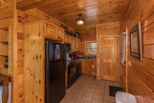 Kitchen with black appliances at Howlin' in the Smokies, a 2 bedroom cabin rental located in Pigeon Forge