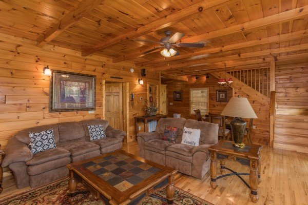 A sofa and loveseat in the living room at Howlin' in the Smokies, a 2 bedroom cabin rental located in Pigeon Forge