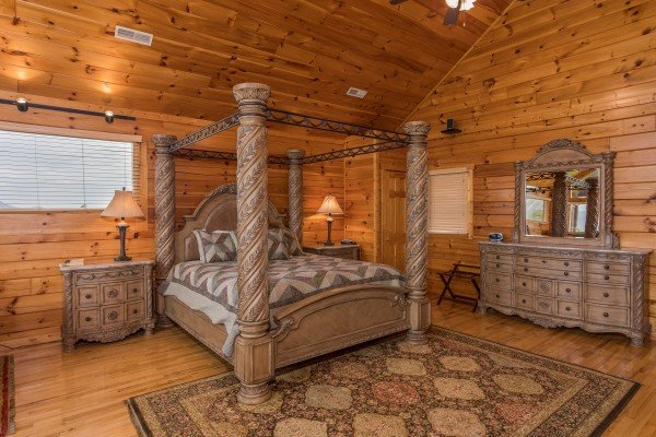 King-sized canopy bed in the loft space at Howlin' in the Smokies, a 2 bedroom cabin rental located in Pigeon Forge